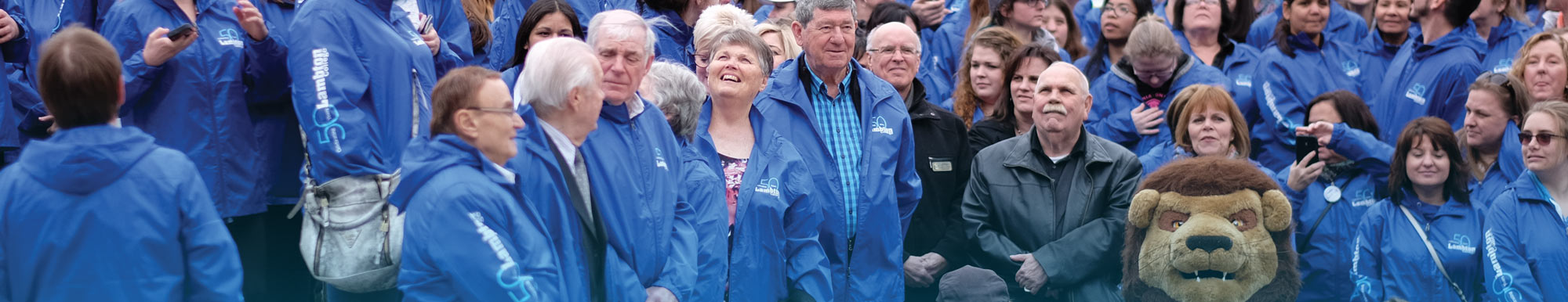 A group of college employees and retirees wearing blue Lambton 50 jackets, gathered around Pounce the mascot