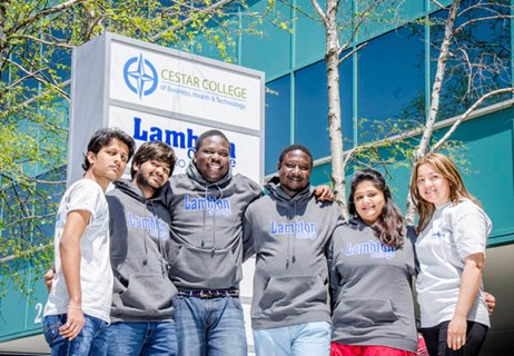 Six students wearing Lambton College attire in front of the Lambton College in Toronto