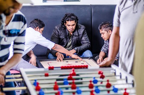 Students sitting down playing a board game together